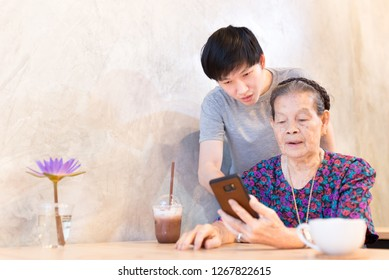 old asian woman and young asian man playing smartphone, they connect internet technology with smartphone, they feeling happy and smile