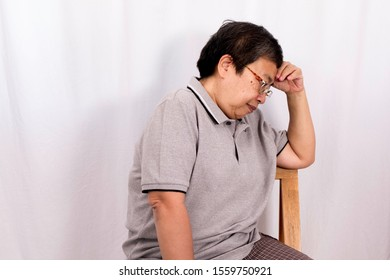 An old Asiatic woman sitting in a chair, hands tightly holding his temples in her head. There are a copy space and isolating. It's on white background.