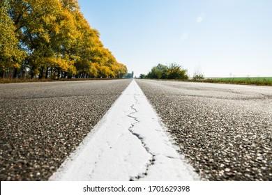Alte Asphaltstraße. Fahren auf einer leeren Straße. Weiße Linie auf der Asphaltstraße gebrochen. Schwache Feldtiefe.