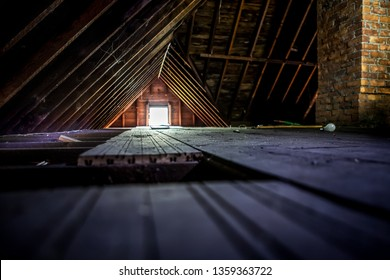 Old attic space with roof rafters and a window, shallow focus on wooden floor