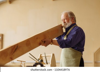 old attractive craftsperson is working with timber indoors. woodworking concept