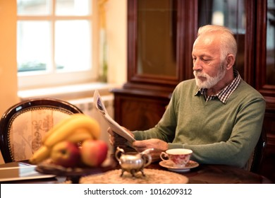 Old attractive senior man sitting at home alone and reading a newspaper, senior man without family