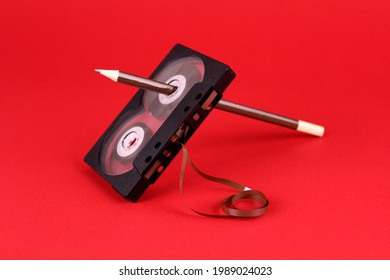 Old audio cassette with a pencil in the hole on a red background. Old rewind cassette tape with tape by pencil