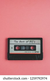 Old audio cassette tape on pink background