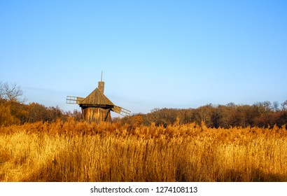 Old authentic traditional wind mill with a reed field and clear sky, Astra Museum of Traditional Folk Civilization, Sibiu city, Transylvania, Romania