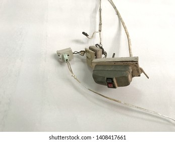 old automatic electrical switch, plug, wire and socket dismantled during renovation and restoration hanging with grunge white wall background of building, obsolete technology without remote control