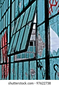 Old automobile plant in Detroit Michigan that has been abandoned. The old windows are broken and covered in graffiti.