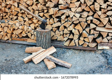 Old ax and a deck for chopping wood. Dry oak firewood stacked in a pile, chopped wood for winter heating of the fireplace. Natural wood background.