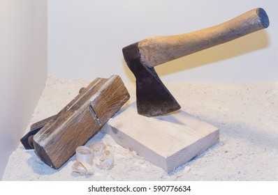 Old ax, planer and shavings on a light background