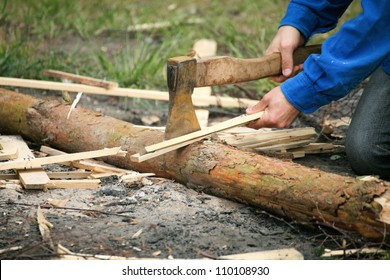 Old Axe stuck in a chopping block and splinters of wood with natural background man