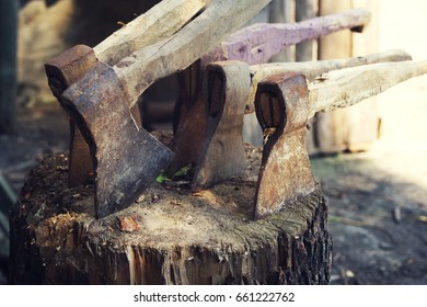Old axes in a woodpile. Collection of old axes