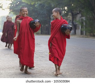 OLD BAGAN, MYANMAR- OCT 15: Two unidentified young novice monks walking morning alms in Old Bagan, Myanmar on October 15, 2011. 89% of the Burmese population is Buddhist.