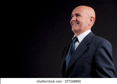 old bald self-confident businessman on a dark background
