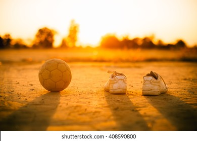 an old ball with the shoes for street soccer football under the sunset ray light.
