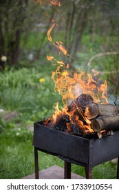 Vieux barbecue grill avec rondins de bois flamboyants. Un feu ouvert depuis une boîte en métal. Pique-nique en plein air dans le parc.