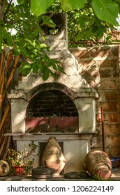 Old barbecue oven, with ancient clay pots and stone millstones, under the trees near the stone wall in the rural courtyard