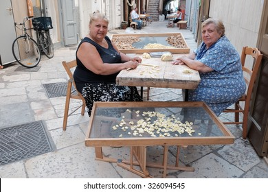 "OLD BARI, ITALY - JULY 06: mother and daughter working the dough to make fresh pasta in the street Arco Basso of Old Bari, also known as the street of ""orecchiette"". Shot in 2015"