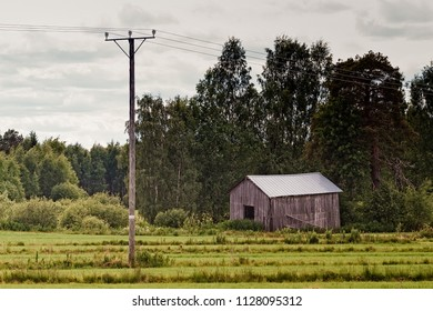 An old barn by the fields at the edge of the forest in the rural Finland. The summer day is turning cloudy.