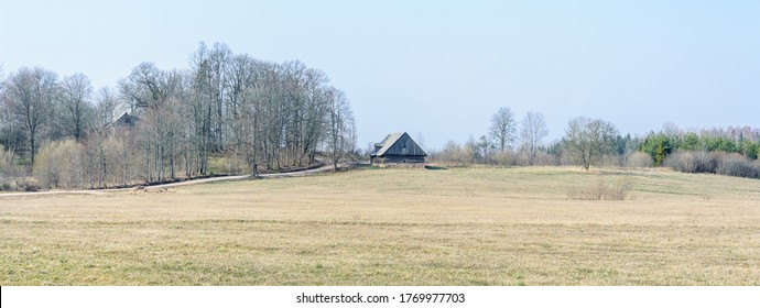 An old barn by a road in the countryside in early spring when the trees are still without leaves