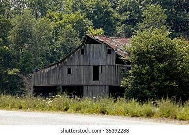 Old Barn, in disrepair, located near highway.