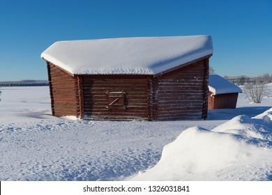 an old barn during winter, with snow and sun