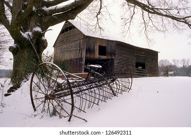 An old barn with farm equipment in the snow