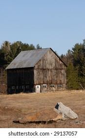 Old Barn with Farmyard with provincial park as background. This is just outside of Algonquin Provincial Park in Ontario, Canada