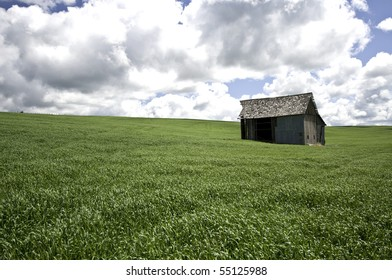 Old barn in  field of green grass and dark clouds above.