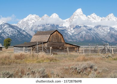 Old barn in front of the snowy mountains