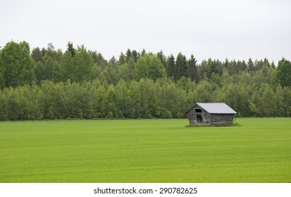 An old barn in a green field. Image taken on a cloudy day.