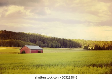 An old barn in a green field next to a forest and hill. Image taken on a partly cloudy day and has a vintage effect applied.