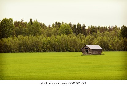 An old barn in the green field in the summer time. Image has a vintage effect.