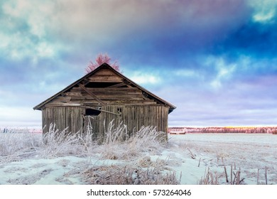 An old barn house on the fields on a very cold winter day in the Northern Finland. It's noon but the sun is already starting to set.