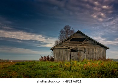 An old barn house stands alone on the autumn fields of the Northern Finland. The skies are getting darker as the winter approaches.