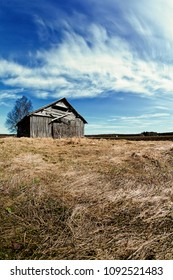 An old barn house stands on the springtime fields of the Northern Finland. The weather is getting warmer, but the nature has not woken up yet.