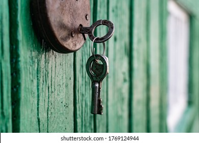 Old barn locks with keys hang on the painted green wood wall. Rusty metal device for closing doors.