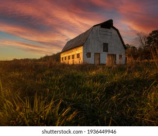 Old Barn in the middle of the country with a beautiful pink and red sunset behind it. Taken in the middle of a field.