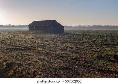 Old barn in misty farmland. Achterhoek. Gelderland. The Netherlands.