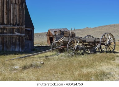 An Old Barn, Outhouse, and Wagon: deep blue sky, and a beautiful field, with an old bar, outhouse, and wagon, in the historic ghost town, Bodie