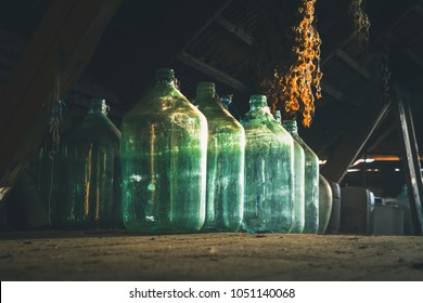 Old barn with a lot of stuff laying around. Sunlight from the window shines upon empty glass bottles. Wooden and aged interior.