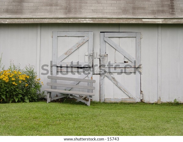 An old barn with sunflowers growing beside it.