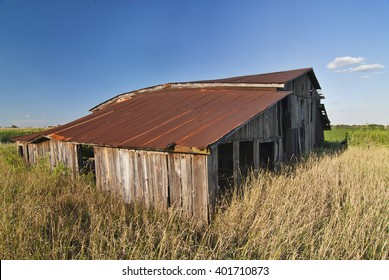 An Old Barn Weathers in the Summer Sun in Will County, Illinois.  This old barn awaits the fate of many such buildings; a new mall and urban development.