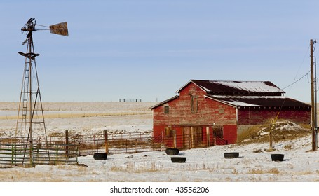 An old barn and windmill on a snowy ranch.