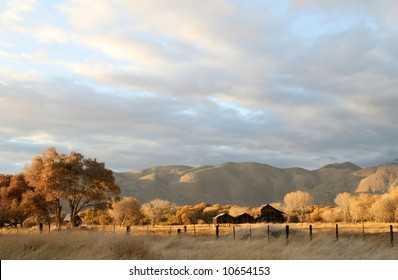 Old barns in quiet field near Onyx, CA on Hwy-178 east of Bakersfield at sunset.