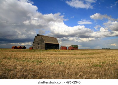 Old Barnyard with stubble field in foreground and a dramatic prairie sky as back drop
