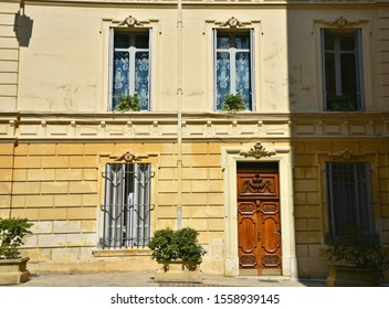 Old Baroque architecture house facade with stone and ochre stucco walls, wooden window shutters and an oak entrance door in Aix-en-Provence Marseille, Provence-Alpes-Côte d'Azur, France.