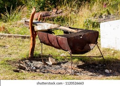 Old barrel bbq - rusty vintage half barrel barbecue