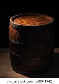 Old barrel on wooden background.