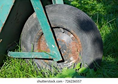 Old barrow wheel in green grass terrain.