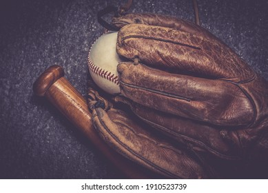 old baseball glove with ball and bat